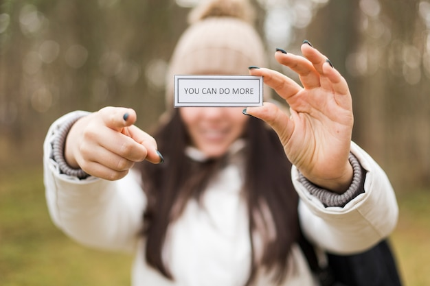 Woman with inspirational writing pointing at camera Free Photo