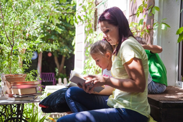 Woman with kids reading on porch Free Photo