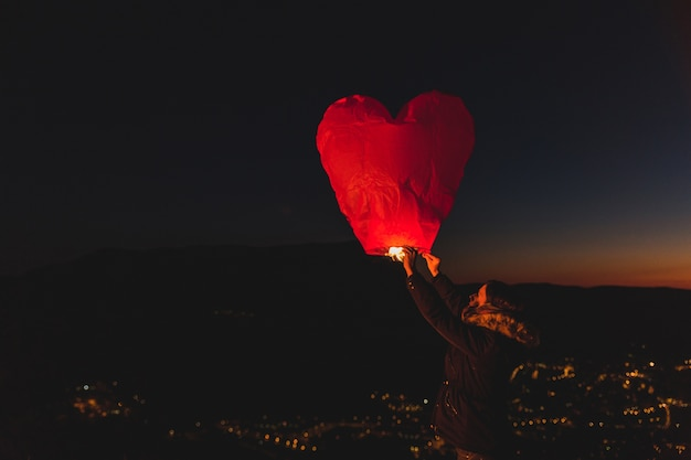 Woman with a kite of hot air at night Free Photo