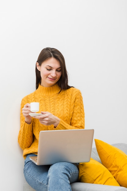 Woman with laptop on lap holding cup of coffee while sitting on the sofa Free Photo