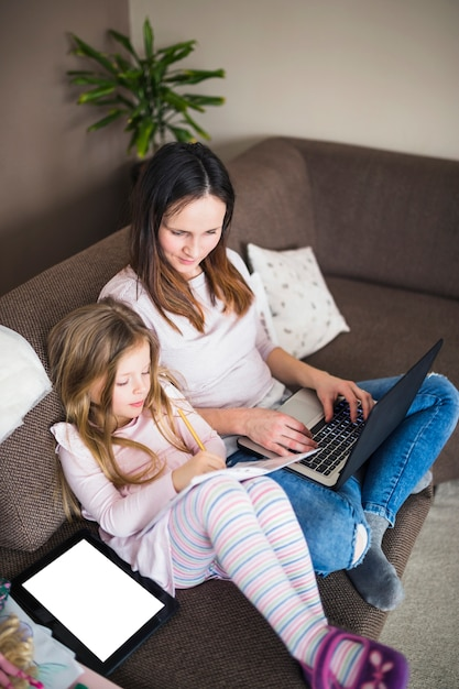 Woman with laptop looking at her daughter studying Free Photo