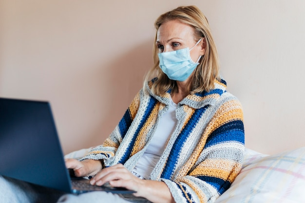 Donna con laptop e mascherina medica in quarantena Foto Gratuite