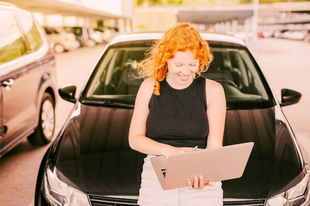 Woman with laptop sitting on hood of car Free Photo