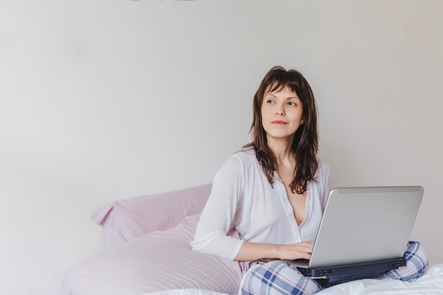 Woman with laptop thinking Free Photo
