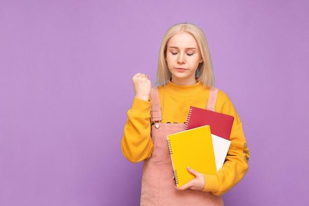 가벼운 머리를 가진 여자는 그녀의 손에 책과 노트북을 들고 화가납니다. 프리미엄 사진