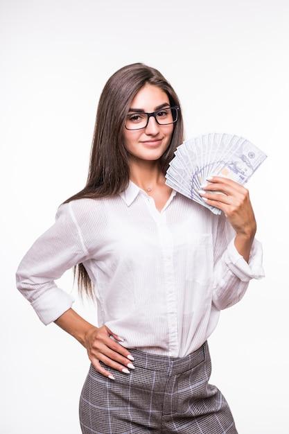 Женщина с длинными каштановыми волосами в повседневной одежде держит много долларовых банкнот над белой Бесплатные Фотографии