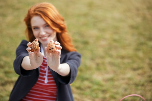 Woman with long ginger hair showing two painted easter eggs Free Photo