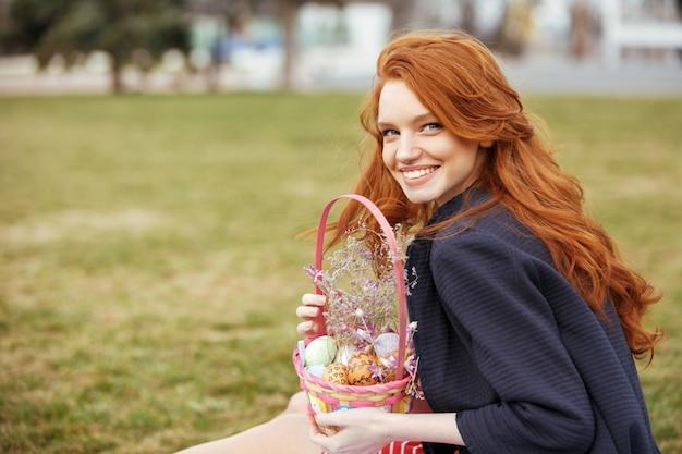 Женщина с длинными волосами держит пасхальную корзину для пикника Бесплатные Фотографии