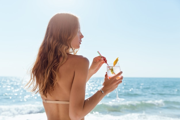 Woman with long hair, holding a wine glass with cocktail, spending vacation Free Photo