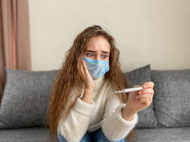 医療マスクで長い髪と彼女の手で温度計を持つ女性。女性は高温で発熱の兆候があります。パンデミックコロナウイルス Premium写真