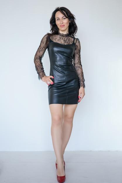 Женщина с длинными волосами в коротком черном платье и красных туфлях Premium Фотографии