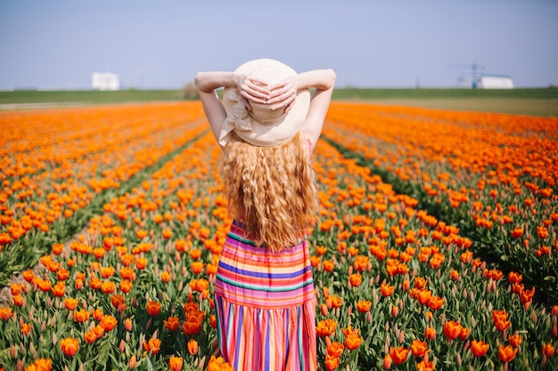Woman with long red hair wearing a striped dress  standing by the back on colorful tulip field. Premium Photo