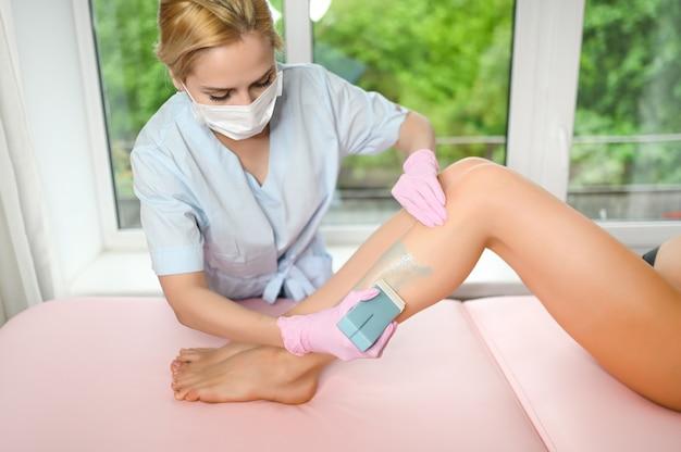 Женщина с длинными загорелыми идеальными ногами и гладкой кожей с восковой полоской для депиляции Premium Фотографии