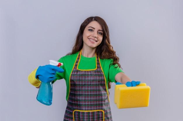 エプロンとゴム手袋をはめた長いウェーブのかかった髪のスポンジを押しながらスプレーを洗浄している女性 無料写真