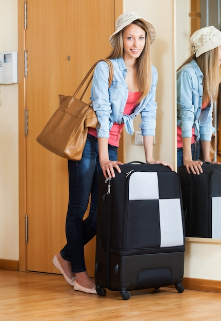 Woman with luggage near door Free Photo