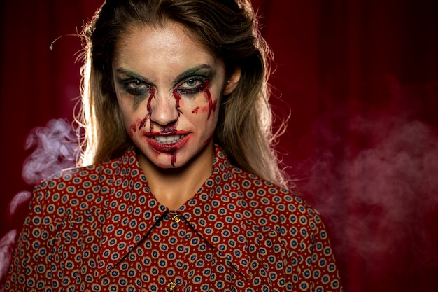 Woman with make-up as blood smirking Free Photo