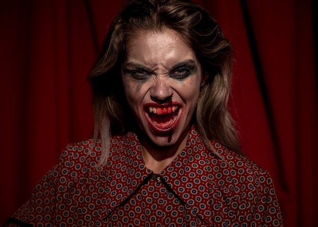 Woman with make-up blood on her face screaming Free Photo