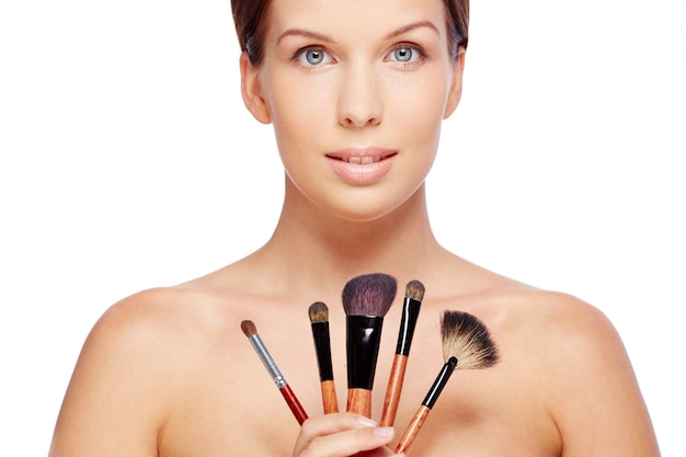 Woman with makeup brushes Free Photo