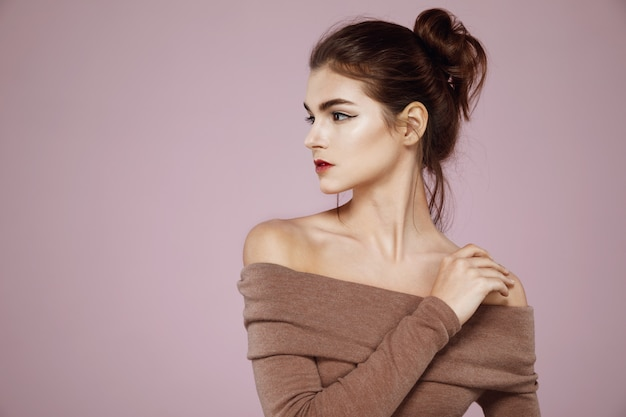 Woman with makeup posing in profile on pink Free Photo
