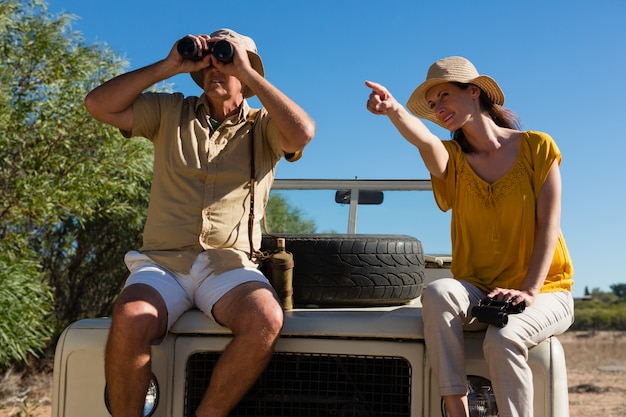 車のボンネットに座って指している男と女 無料写真