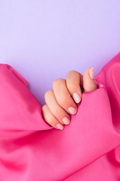 コピースペースのあるピンクの布を持ってマニキュアをした女性 無料写真