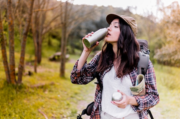 Woman with map drinking from thermos Free Photo