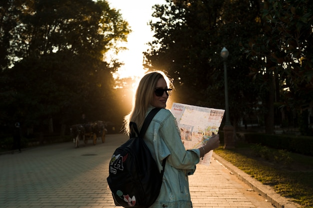 Woman with map in park on sunset Free Photo
