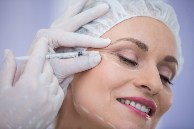 Woman with marked face receiving botox injection Free Photo