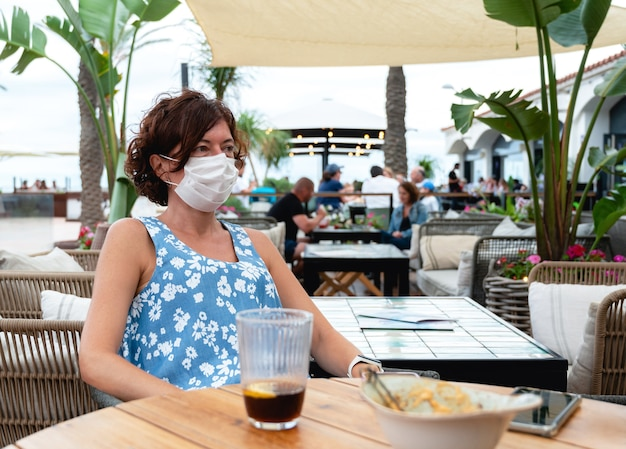 Женщина с маской на террасе с содовой Premium Фотографии