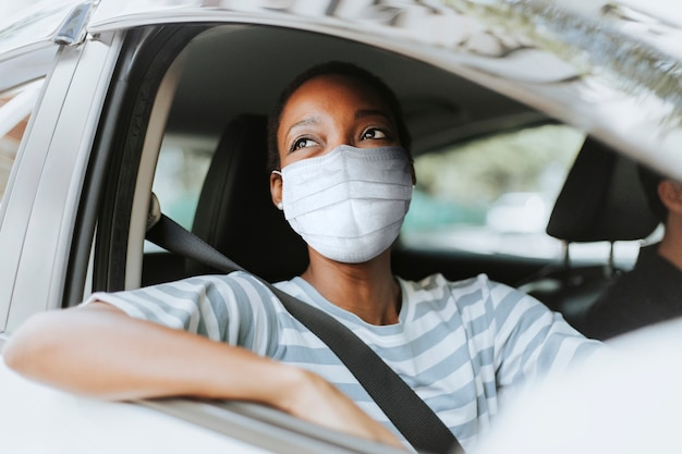 Woman with mask at drive thru with her car Free Photo