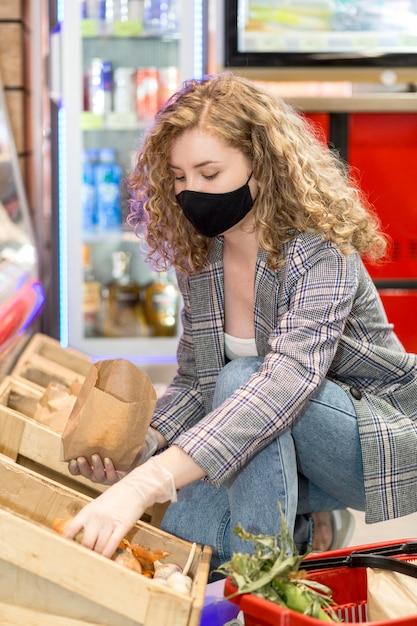 Donna con la maschera alla drogheria di acquisto del mercato Foto Gratuite