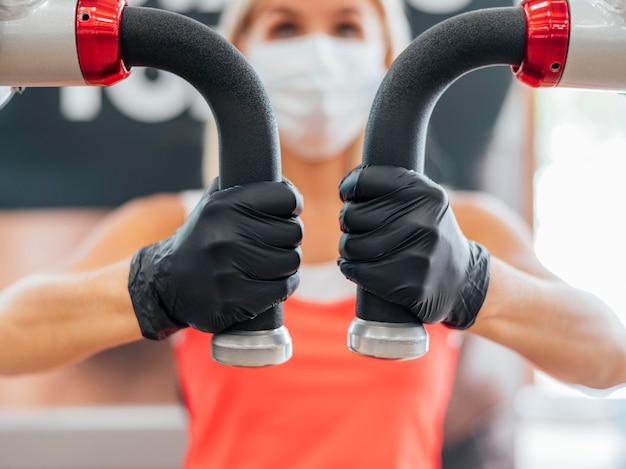 ジムのトレーニングで医療マスクと手袋を持つ女性 無料写真