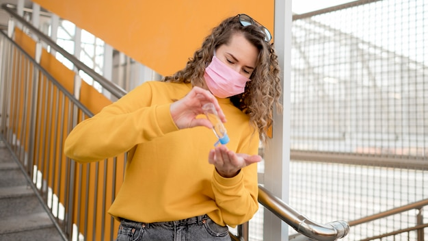 Женщина с медицинской маской и с помощью дезинфицирующего средства для рук Бесплатные Фотографии