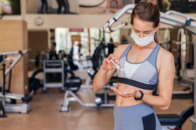 Женщина с медицинской маской в тренажерном зале, используя дезинфицирующее средство для рук Бесплатные Фотографии