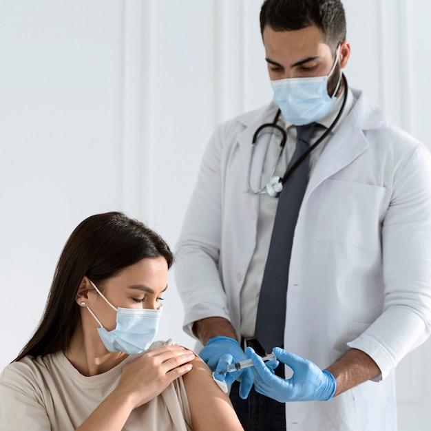 Donna con mascherina medica vaccinata dal medico Foto Gratuite