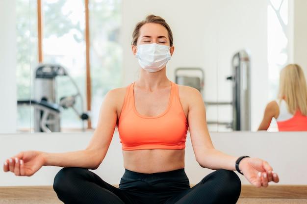 Женщина с медицинской маской занимается йогой в тренажерном зале Бесплатные Фотографии