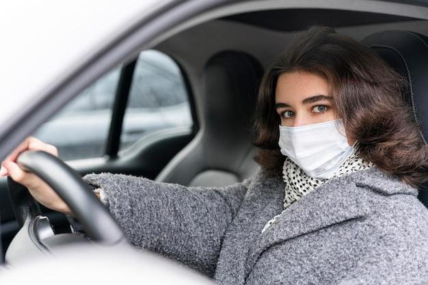 車を運転する医療マスクを持つ女性 無料写真