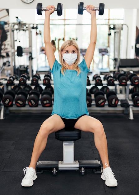 체육관에서 유행병 동안 운동 의료 마스크를 가진 여자 무료 사진