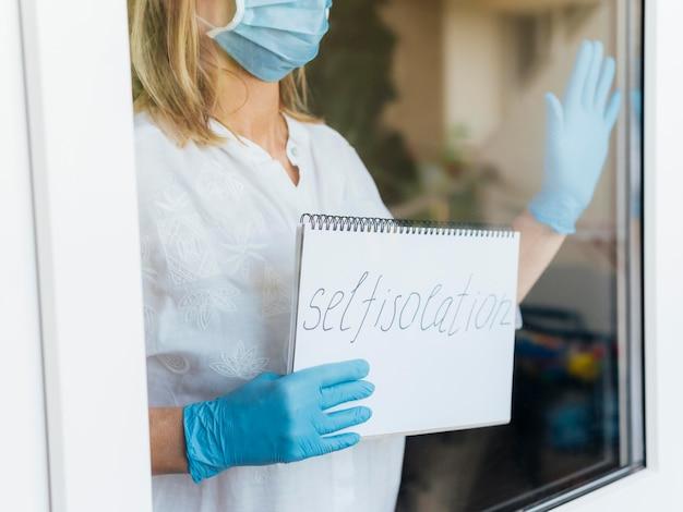 Donna con maschera medica e guanti che tengono taccuino domestico di soggiorno Foto Gratuite