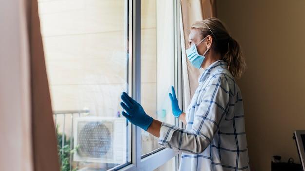 Donna con maschera medica e guanti a casa guardando attraverso la finestra Foto Gratuite