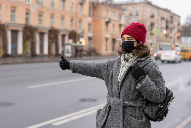Donna con maschera medica autostop in città Foto Gratuite