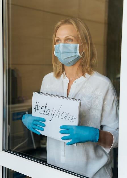 Donna con la mascherina medica che tiene il taccuino domestico di soggiorno alla finestra Foto Gratuite