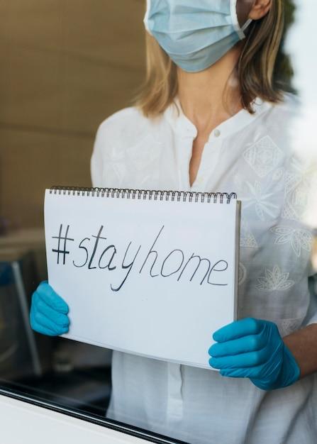 Donna con la mascherina medica che tiene taccuino domestico di soggiorno Foto Gratuite