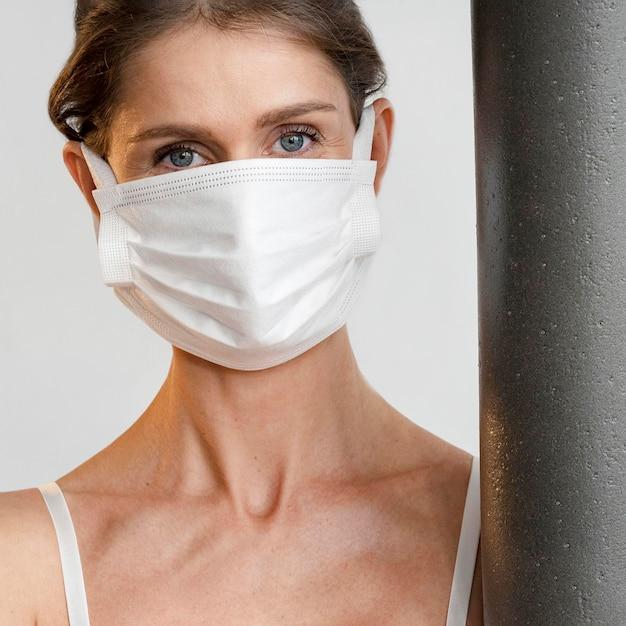 Donna con mascherina medica azienda materassino yoga Foto Gratuite