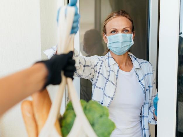 Donna con maschera medica a casa a prendere la spesa in autoisolamento Foto Gratuite