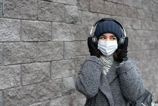 ヘッドフォンで音楽を聴いている街の医療マスクを持つ女性 無料写真