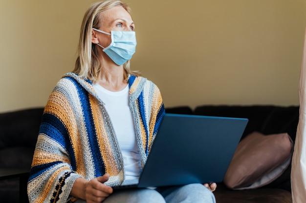 Donna con maschera medica e laptop in quarantena a casa Foto Gratuite