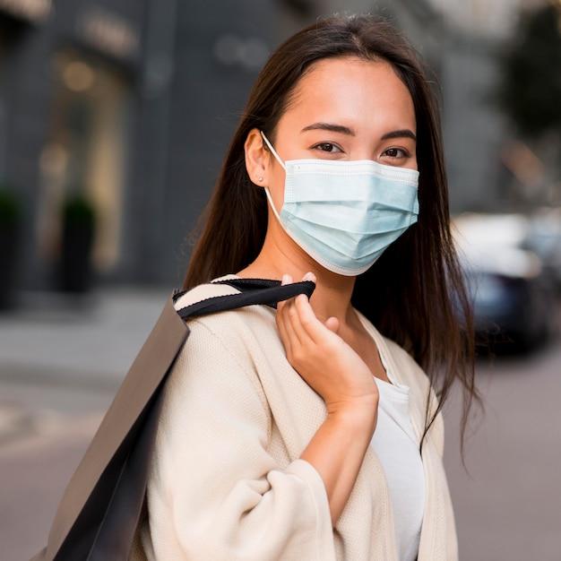 Donna con maschera medica fuori per una baldoria di shopping di vendita con il sacchetto della spesa Foto Gratuite