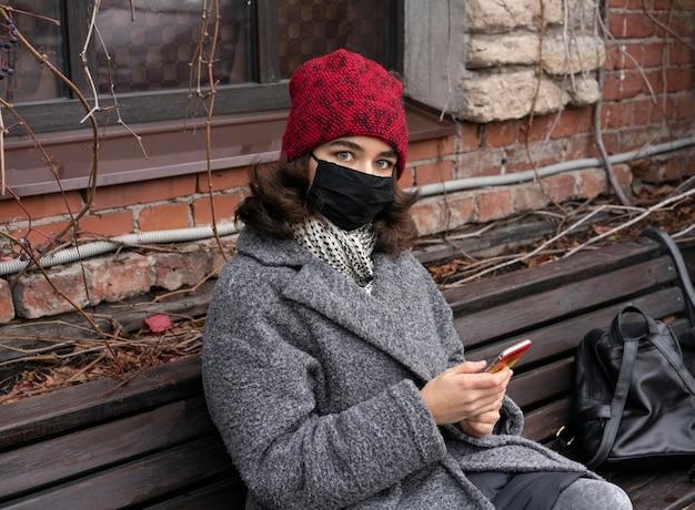 Donna con mascherina medica all'aperto sul banco utilizzando smartphone Foto Gratuite