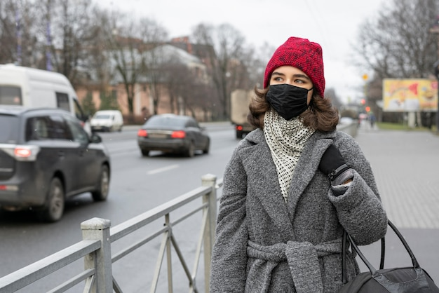 Donna con mascherina medica all'aperto in città Foto Gratuite